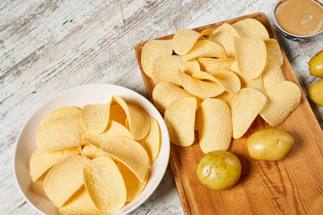 Homemade fresh chips and young raw potatoes on the cutting board