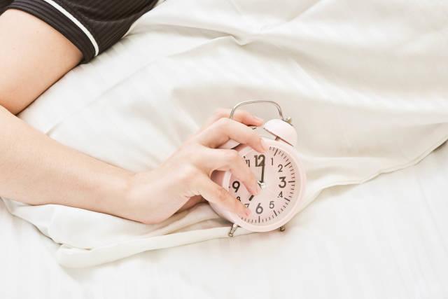 Sleepy female trying kill alarm clock