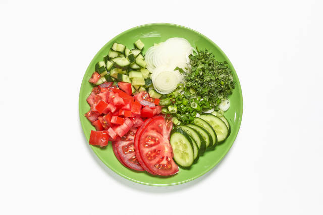 A plate of sliced tomatoes, cucumbers, onions and greens
