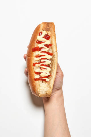 A person hand holding tasty hot dog with mustard and ketchup on white background