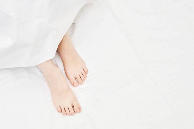 Top view on the sleeping woman legs under blanket