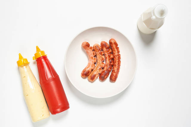 Fried hot-dog sausages and sauces on white