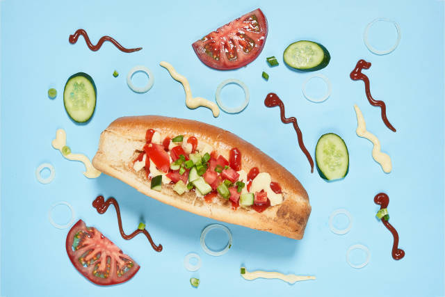 Tasty hotdog and ingredients on blue background