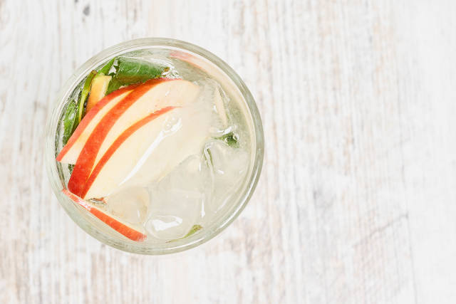 A glass of soft cooling summer drink with apple slices and mint leaves