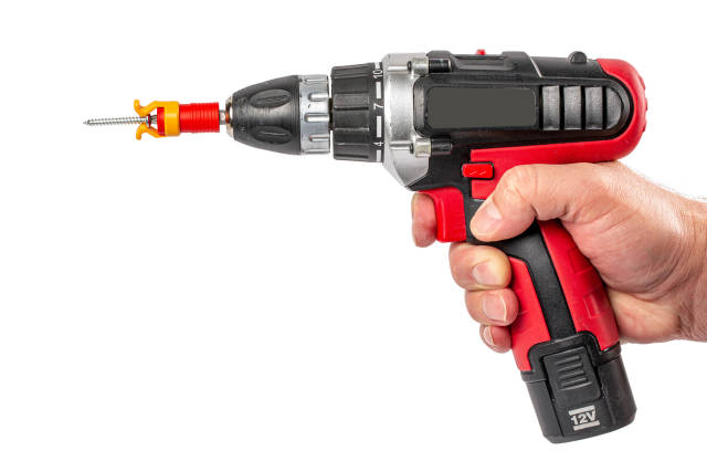 Electric screwdriver with screw holder in man hand