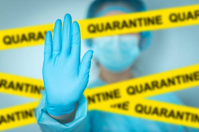 Concept quarantine alert with blurred doctor with mask and protective suit, doctor and isolation with yellow ribbons for quarantine