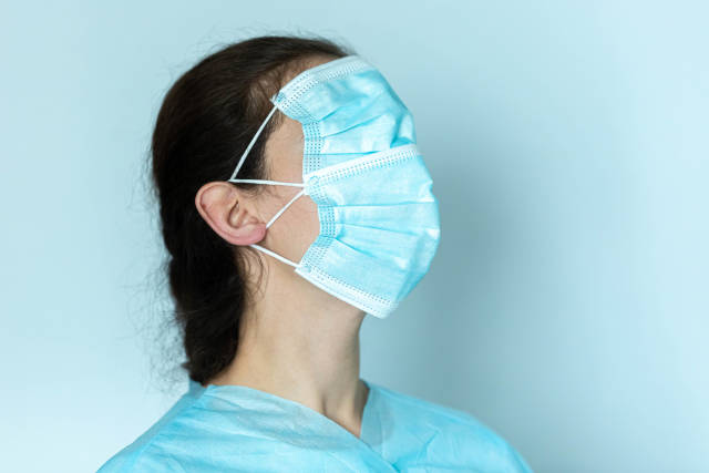 Young woman wearing two medical face mask over her eyes, nose and mouth