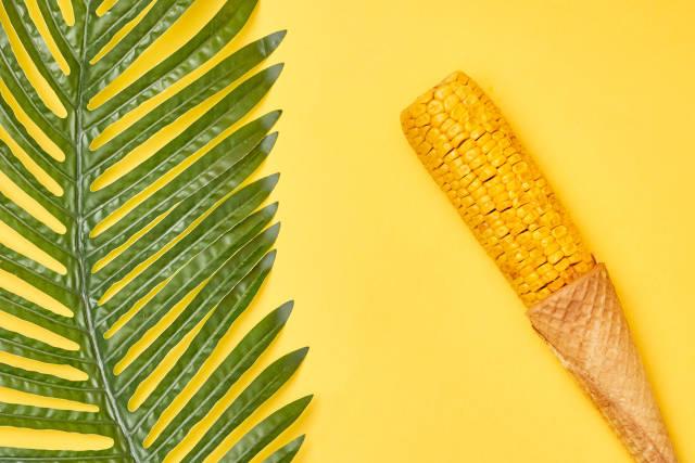 Swing of corn in ice cream waffle cone on yellow