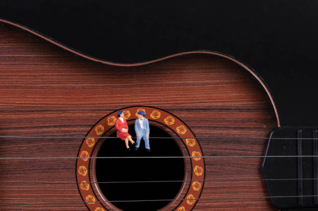 Couple sitting on a guitar