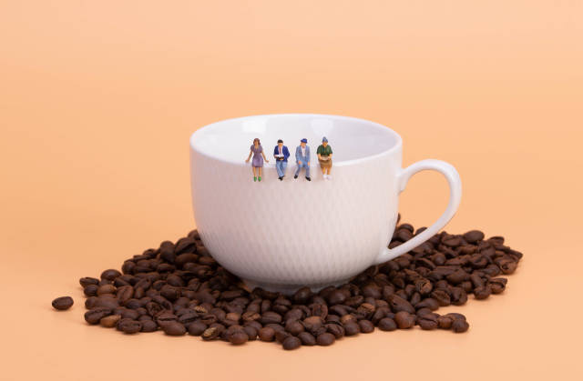 Miniature people: business team sitting on cup of coffee with morning news. Coffee time of business concept.