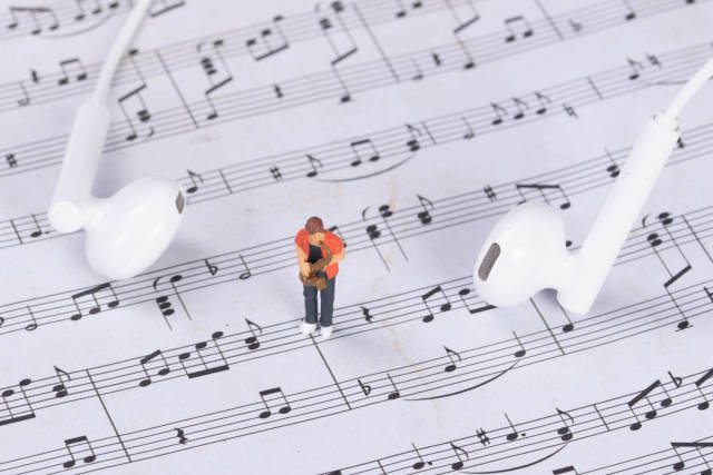 Miniature saxofonist with earbuds on music notes