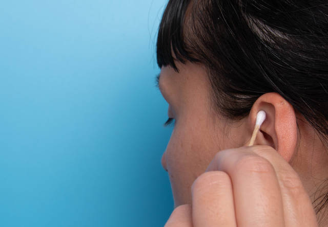 Girl cleaning her ear with a cotton swab on blue background