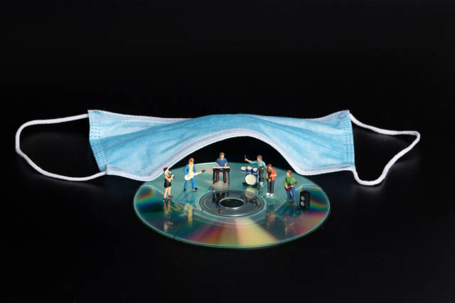 Miniature rock band and medical face mask on black background