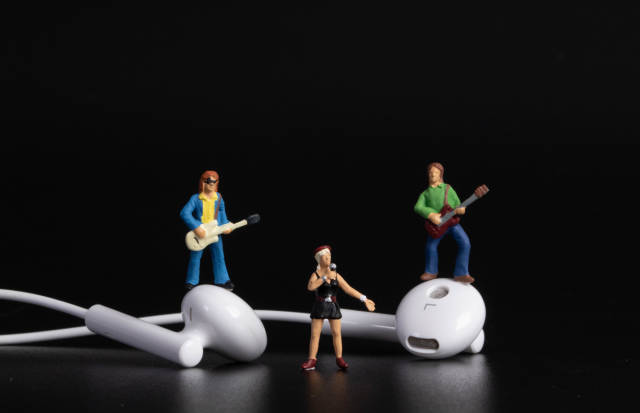 Miniature band with earbuds on black background