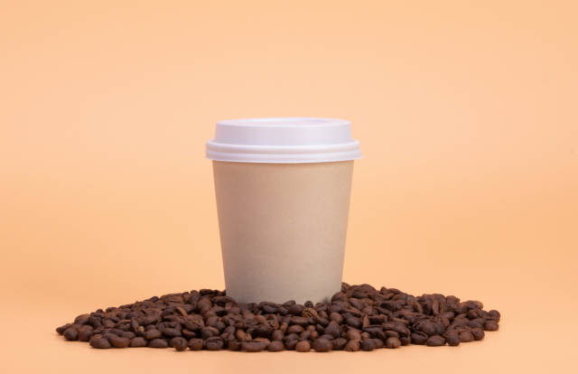 Paper cup of coffee and coffee beans