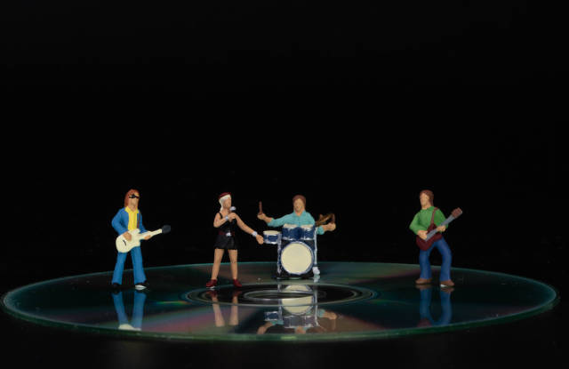 Miniature band standing on CD on black background