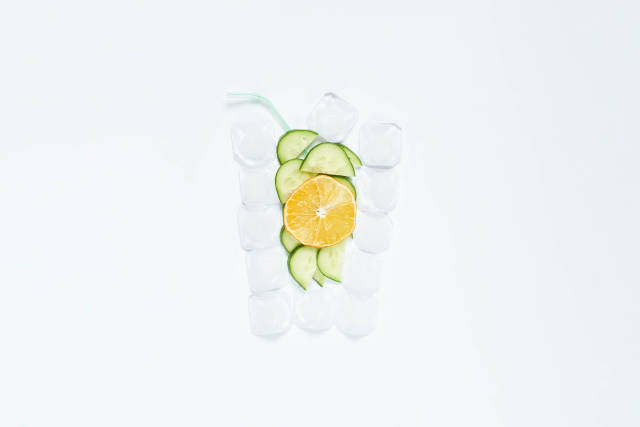Creative summer drink shape made of ice cubes, cucumber and lemon slices