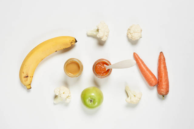 Banana and carrot-based purees with apple fruit and broccoli on white