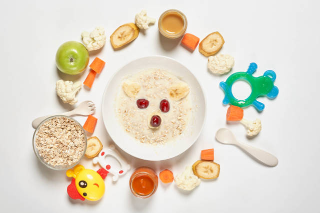 Homemade organic baby porridge and a pile of toys, vegetables and fruit cuts around