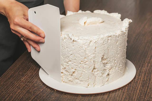 Female hands line creamy coating on cake, homemade baking