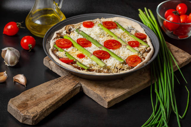Raw pie with minced meat, mushrooms, cheeses and vegetables on a dark background