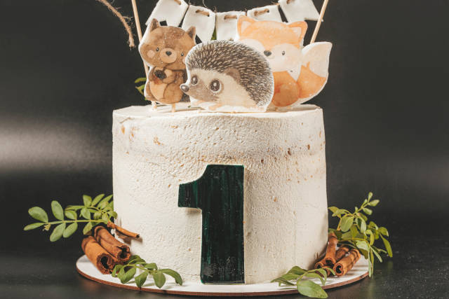 Childs birthday cake decorated with animal figurines on a dark background