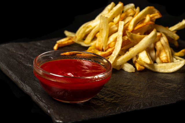 Tomato sauce and fried fries on black background
