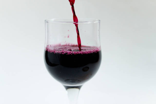Close Up Photo of Wine Glass being filled up with Red Wine on White Background