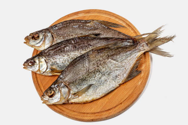 Dry fish on wooden background, top view