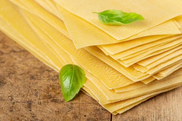 Close-up, raw lasagna sheets, old wood background