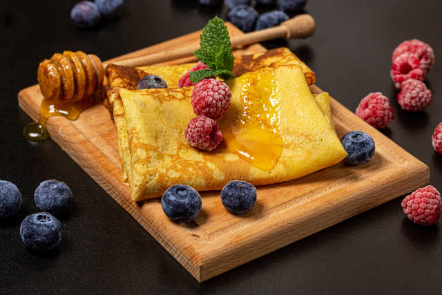 Pancakes with raspberries, blueberries and honey
