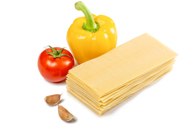 Dry lasagna sheets with garlic, bell pepper and tomato on a white background