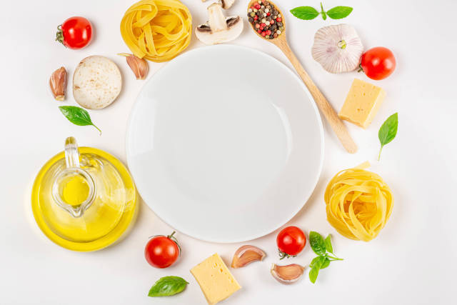 Top view of pasta, raw vegetables and spices on white background with empty plate in the middle