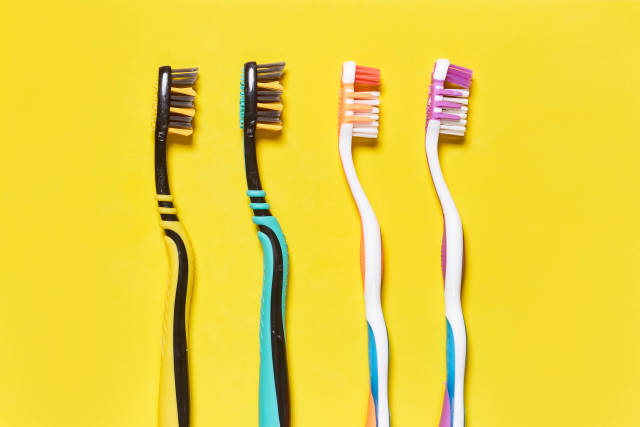A row of toothbrushes on bright yellow background