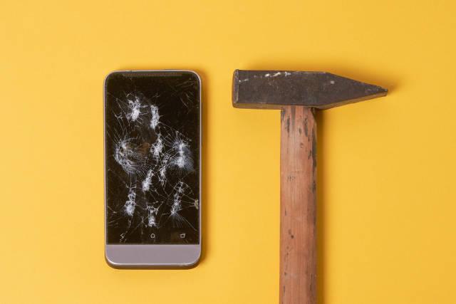 Broken phone and hammer