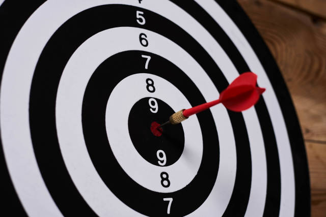 Dart arrow hitting on target center on bullseye in wooden dartboard