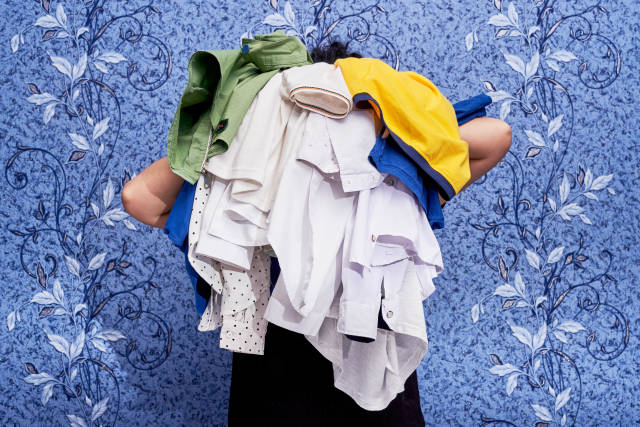 Housewife holding a pile of laundries