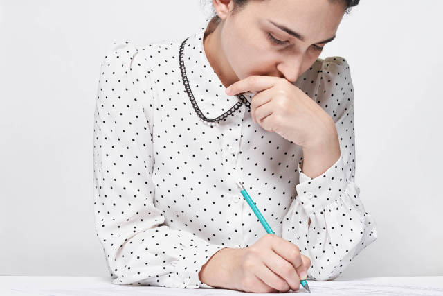 Young thoughtful woman doing test for job employment