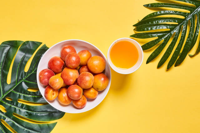 A bowl of fresh and organic apricot fruits with a cup of sweet apricot juice