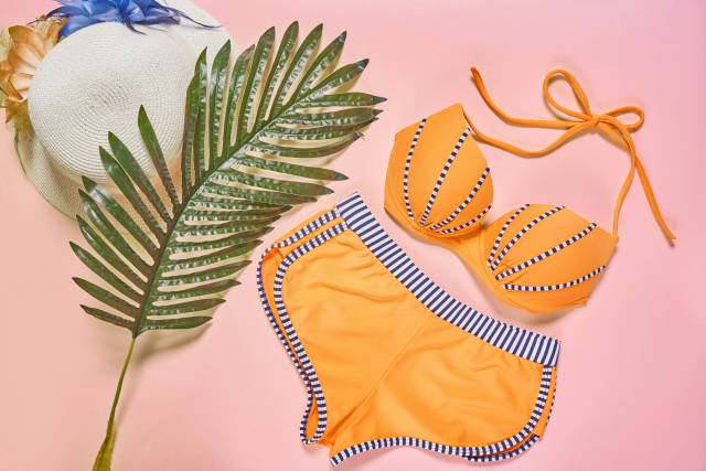 Swimsuit and beach items on pink