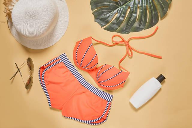 Cute females bikini, sunglasses, straw hat and sunscreen cream on colored background