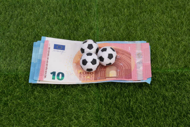 Euro banknotes with soccer balls on green grass
