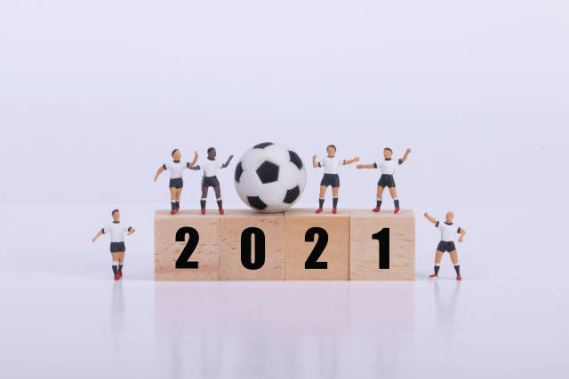 Soccer players standing on wooden cubes with 2021 text on white