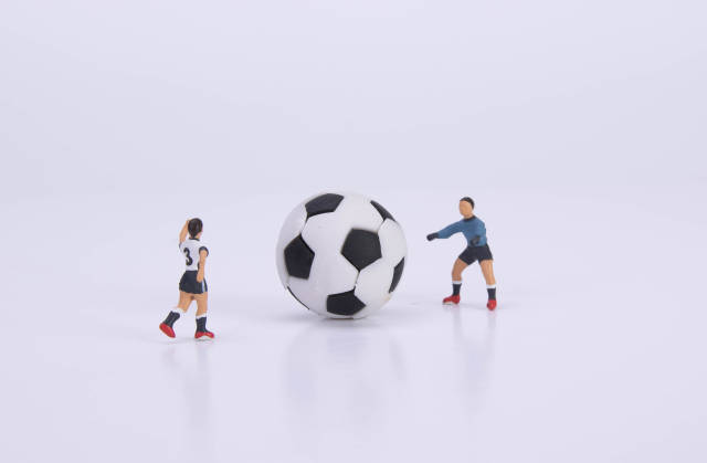 Football player and goalkeeper with ball on white background