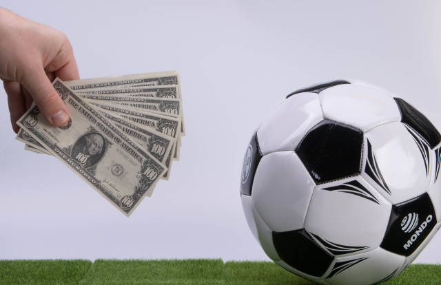 Hand holding 100 Dollars banknotes and soccer ball on white background