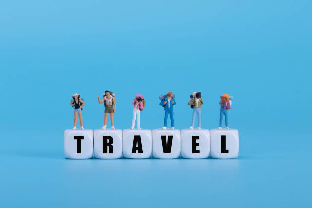 Travelers standing on white blocks with Travel text on blue background