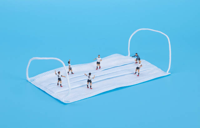 Soccer players playing football on medical face mask