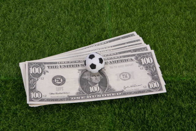 US dollar banknotes with soccer ball on green grass