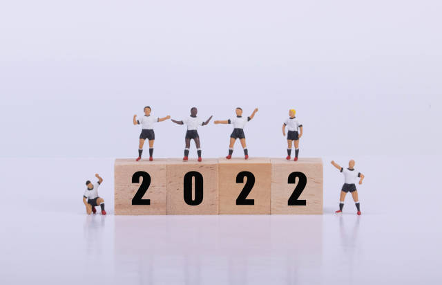 Soccer players standing on wooden cubes with 2022 text
