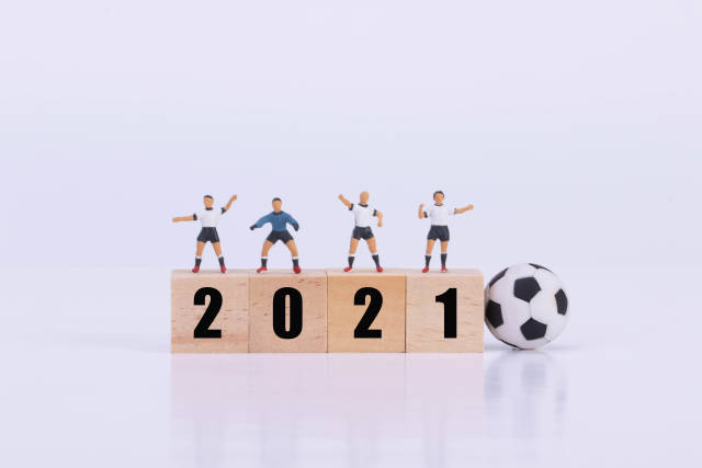 Football players standing on wooden cubes with 2021 text